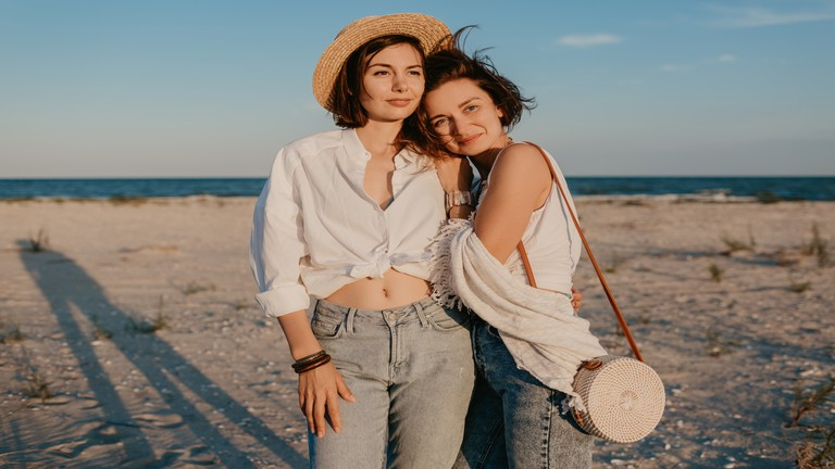 two young women having fun on the sunset beach, queer non-binary gender identity, gay lesbian love romance, boho summer vacation style wearing jeans